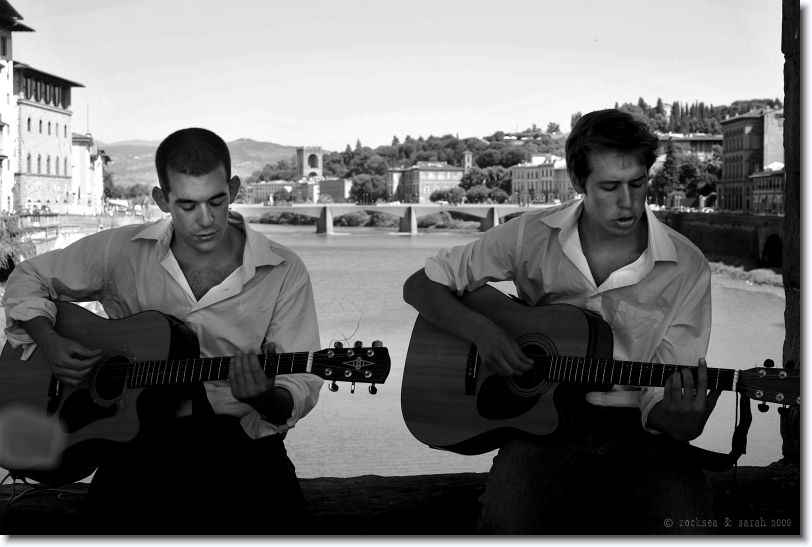 Playing Guitars at the bridge on River Arno in Florence, Italy