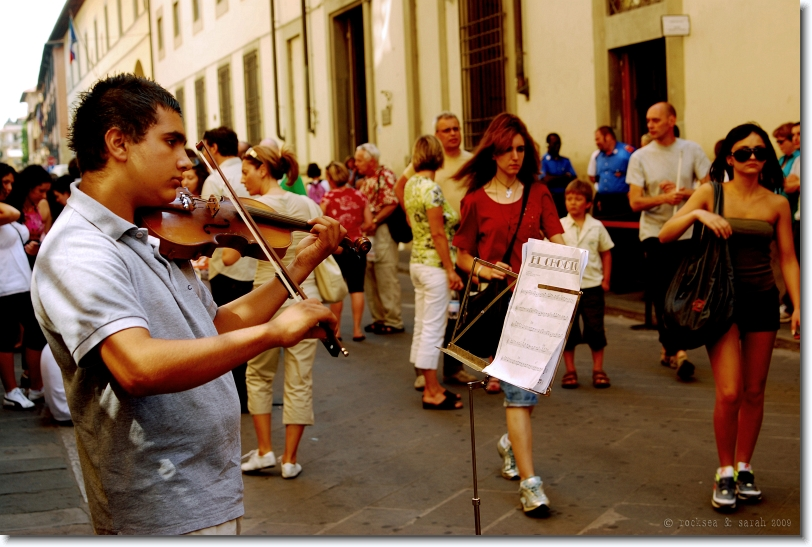 A boy playing El Choclo on Violin, before the museum Galleria dell'Accademia in Florence, Italy